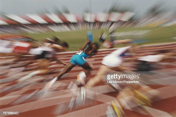 Zoom pull view of male sprinters accelerating from their starting blocks in the first seconds of a 100 metres race at an athletics track circa 1990
