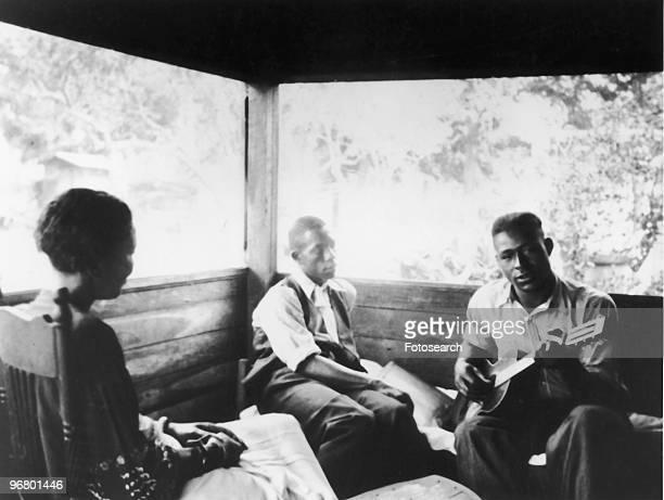 Zora Neale Hurston listening and friends sitting indoors listening to music circa 1950s