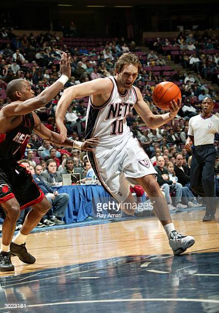 Zoran Planinic of the New Jersey Nets drives to the basket against Loren Woods of the Miami Heat February 28 2004 at the Continental Airlines Arena...