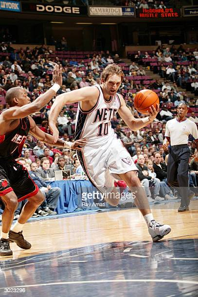 Zoran Planinic of the New Jersey Nets drives to the basket against Loren Woods of the Miami Heat on February 28 2004 at the Continental Airlines...