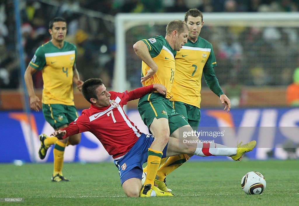 Zoran Tosic of Serbia tackles Scott Chipperfield of Australia during the 2010  FIFA World Cup South b5320e930ea78