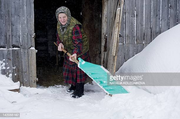 Zoya Dorodova a member of the singing group Buranovskiye Babushki shovels snow near her home in the village of Buranovo in the central Russian region...
