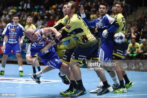 Zsolt Balogh of Szeged throws the ball under pressure from Kim Ekdahl du Rietz of RheinNeckar Loewen during the EHF Champions League match between...