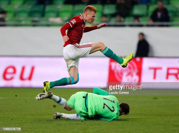 Zsolt Kalmar of Hungary jumps over goalkeeper Jesse Joronen of Finland during the UEFA Nations League group stage match between Hungary and Finland...