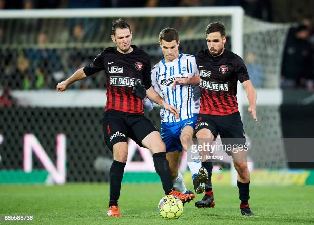 Zsolt Korcsmar of FC Midtjylland Nicklas Helenius of OB Odense and Filip Novak of FC Midtjylland compete for the ball during the Danish Alka...