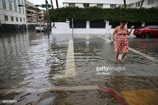 Zsuzsa Nagy walks through a flooded street that was caused by the combination of the lunar orbit which caused seasonal high tides and what many...