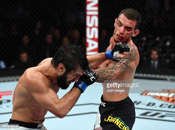 Zubaira Tukhugov of Russia punches Renato Moicano of Brazil in their featherweight bout during the UFC 198 event at Arena da Baixada stadium on May...
