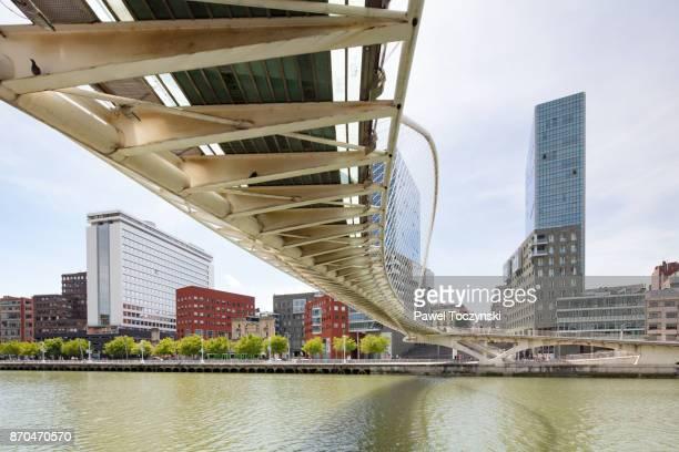 Zubizuri bridge designed by Santiago Calatrava over Nevrion river in Bilbao, with Torres Isozaki in the background