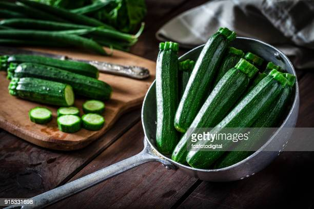zucchini in an old metal colander - zucchini stock pictures, royalty-free photos & images
