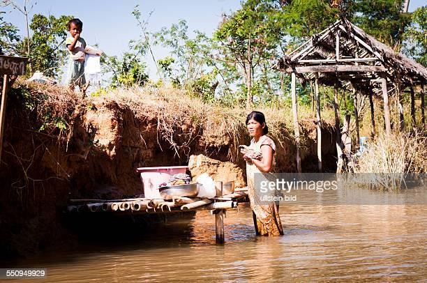 Zufluss zum Inle See Frau beim Waesche waschen