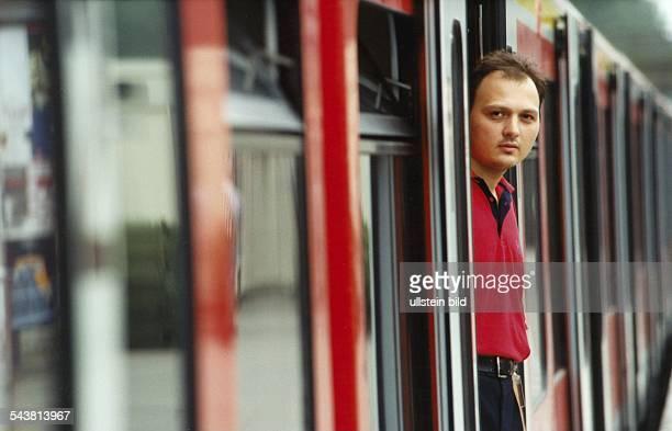 Zugbegleiter Turgut Gökmen von der Hamburger SBahn steht in der Tür eines SBahnwagens und blickt auf den Bahnsteig Er trägt das rote Uniformhemd der...