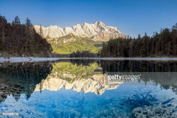 zugspitze and eibsee-garmisch-partenkirchen, fish is crossing the picture - upper bavaria stock photos and pictures