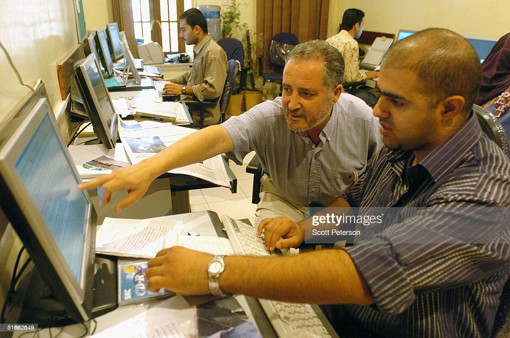 Zuhair al-Jizary, editor of Baghdad's Al-Mada newspaper, speaks with typist Saif Adil, in the small newsroom of Al-Mada on October 21, 2004 in Baghdad, Iraq. Iraqi journalists are enjoying unprecedented freedom in post-Saddam Iraq, though they are also frequently targeted with death threats by Iraq's lawless political and religious factions.
