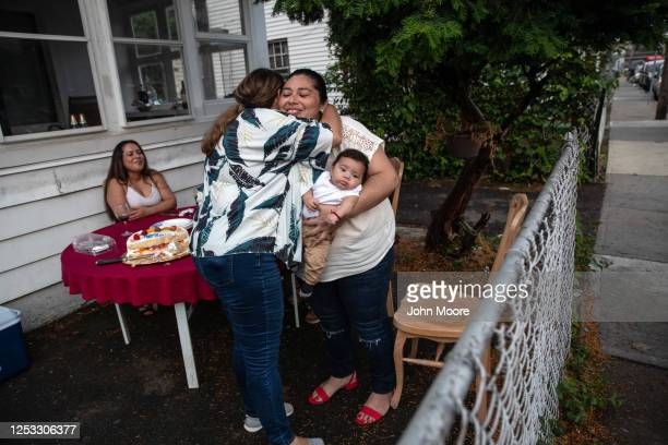 Zully holds her son Neysel 10 weeks while embracing elementary school teacher Luciana Lira following a dinner celebrating Neysel's three month...