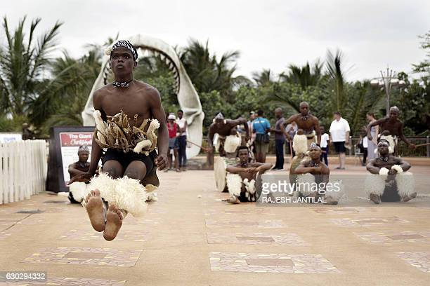 A Zulu dancer gestures during a traditional dance show for tourists on December 20 2016 at Africa's largest and biggest Marine theme park the uShaka...