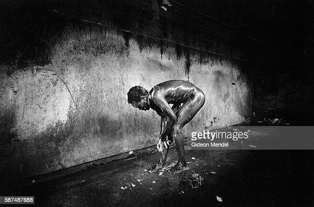 A Zulu migrant worker washes himself at the communal showers at Nancefield Hostel in Soweto South Africa Migrant workers spend most of their time...