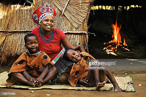zulu woman in traditional red headdress of a married woman with her children. beehive hut in the background. lesedi cultural village near johannesburg, south africa. - zulu women stock pictures, royalty-free photos & images