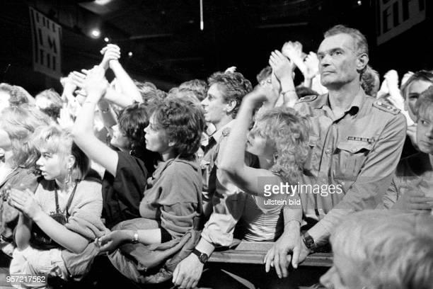 Zumeist jüngere Menschen amüsieren sich bei einem Rockkonzert im Palast der Republik in Ost-Berlin, aufgenommen 1987.