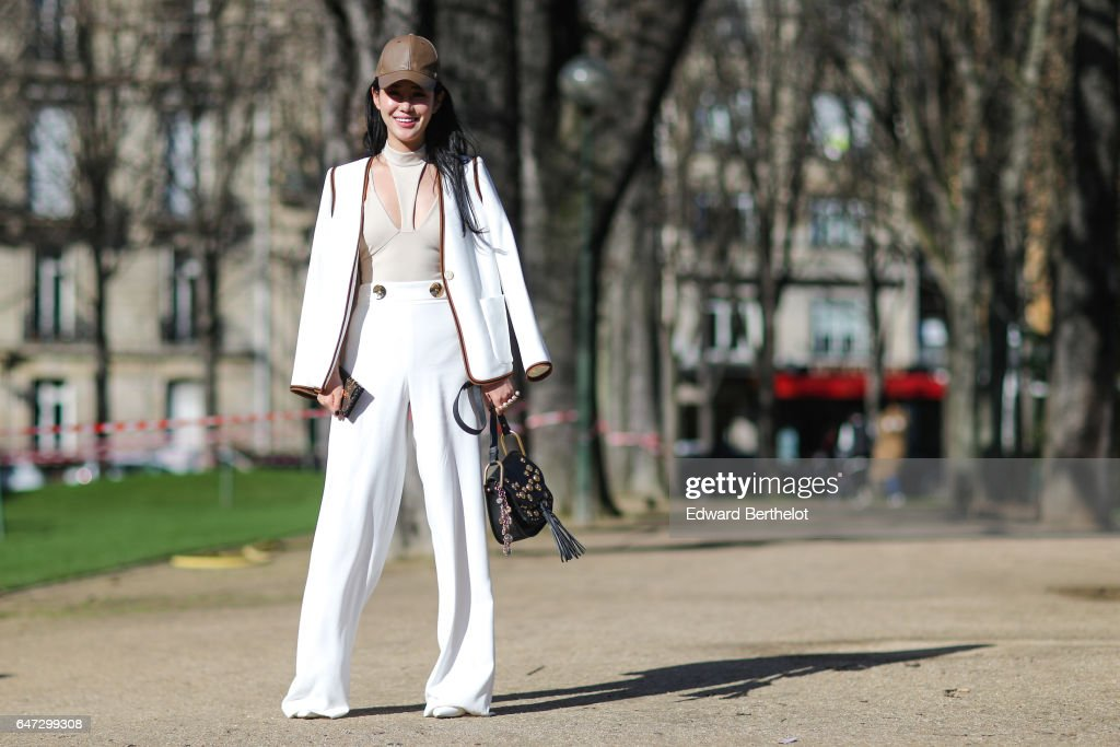 Zuo An Xiao wears a white jacket, white pants, and a brown cap, outside the Chloe show, during Paris Fashion Week Womenswear Fall/Winter 2017/2018, on March 2, 2017 in Paris, France.