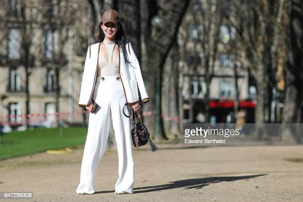 Zuo An Xiao wears a white jacket white pants and a brown cap outside the Chloe show during Paris Fashion Week Womenswear Fall/Winter 2017/2018 on...