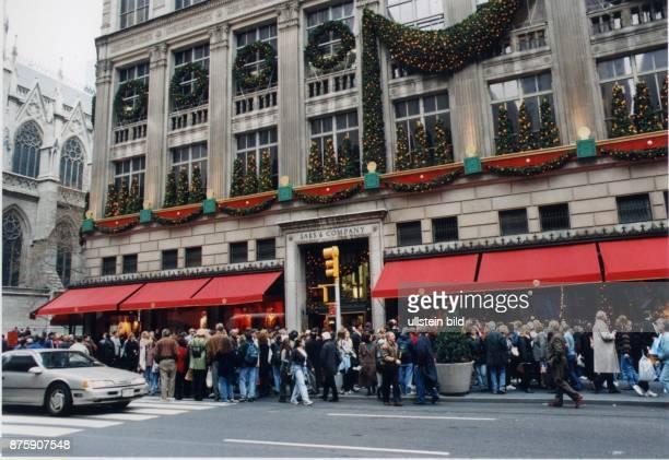 Zur Adventszeit in New York drängen sich Menschen auf dem überfüllten Bürgersteig vor dem weihnachtlich dekorierten Geschäft Saks und Company...