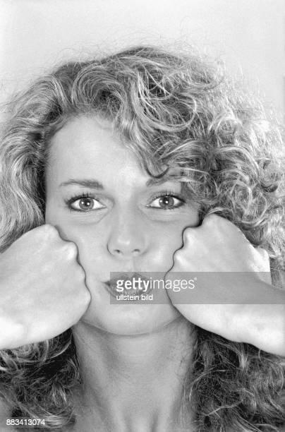 Zur Kräftigung der Wangenmuskulatur drückt eine Frau ihre geballten Fäuste in ihre aufgepusteten Wangen und drückt langsam die Luft hinaus Dieses...