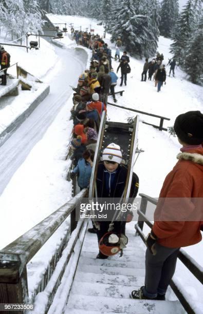 Zur VII Kinder und Jugendspartakiade im Februar 1979 betritt ein junger Rodler mit seinem Schlitten auf dem Rücken die Treppe zur Abfahrt auf der...