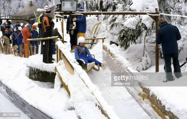 Zur VII Kinder und Jugendspartakiade im Februar 1979 startet ein junger Rodler auf seinem Schlitten die Abfahrt auf der vereisten Rennrodelbahn in...