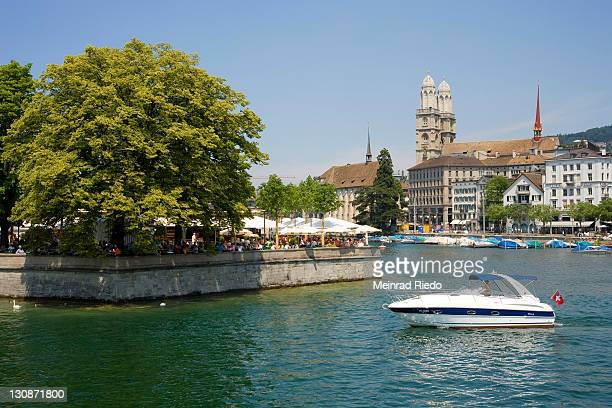 Zurich on Lake Zurich, Switzerland. In the background the Grossmuenster cathedral. Terraced restaurant under shady trees. Motor boat with swiss flag