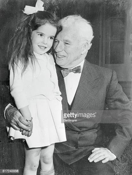 Zurich, Switzerland: Just turned 65, filmdom's great comedian Charles Chaplin accepts a birthday hug from his daughter, Josephine. Chaplin and his...