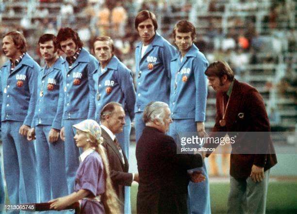 Zusammen mit dem brasilianischen FIFA-Präsidenten Joao Havelange überreicht der irische IOC-Präsident Lord Killanin dem einzigen Spieler, der von der...