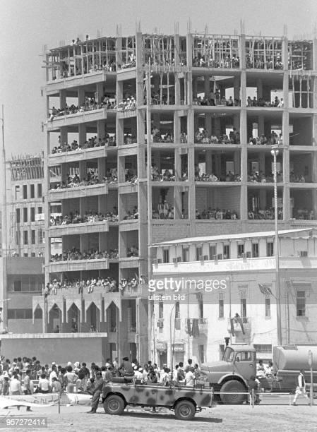 Zuschauer am Rande der Straße und in den Etagen eines im Rohbau stehenden Gebäudes verfolgen eine Militärparade der libyschen Streitkräfte in Bengasi...