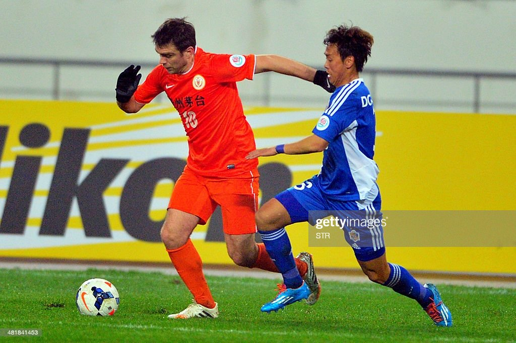 Zvjezdan Misimovic (L) of China's Guizhou Renhe tussles for the ball against Jeong Dong-ho of South Korea's Ulsan Hyundai during their AFC Champions League group H first round match at the Guiyang ...