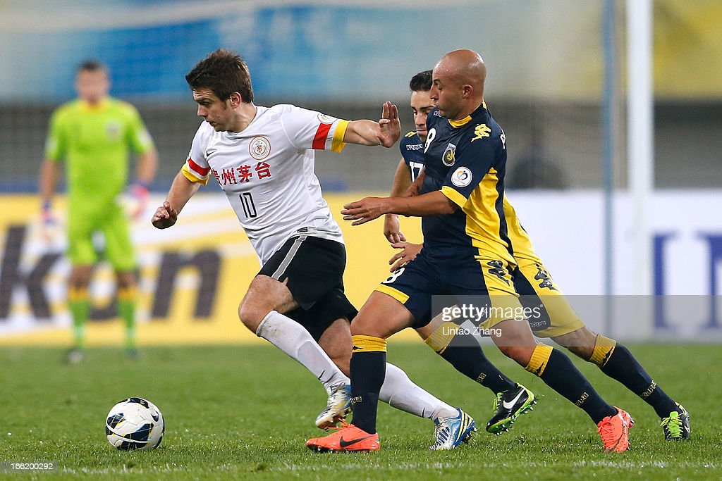 Zvjezdan Misimovic (L) of Guizhou Renhe challenges Adriano Pellegrino and Anthony Caceres of the Mariners during the AFC Champions League match between Guizhou Renhe and Central Coast Mariners at Olympic Sports Center on April 9, 2013 in Guiyang, China.