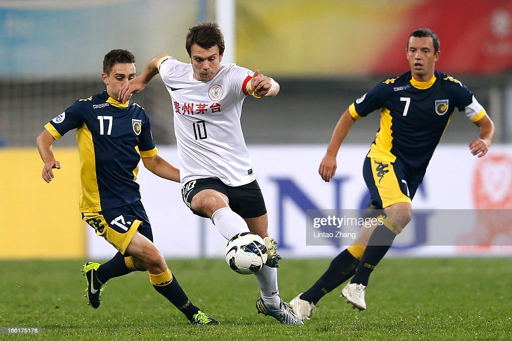 Zvjezdan Misimovic (C) of Guizhou Renhe controls the ball with Anthony Caceres (L) and John Hutchinson of Mariners during the AFC Champions League match between Guizhou Renhe and Central Coast Mariners at Olympic Sports Center on April 9, 2013 in Guiyang, China.