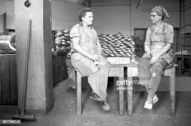 Zwei Arbeiterinnen sitzen auf Tischen und gönnen sich eine Arbeitspause mit Zigarette und Milch aufgenommen am in der Felgenschleiferei des zum...