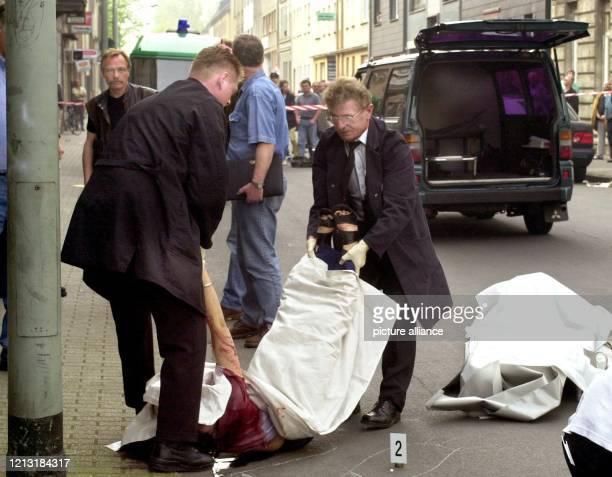 Zwei Bestatter heben am 2842000 in Duisburg die Leiche einer jungen Frau auf eine Bahre Die 36jährige Frau afghanischer Herkunft wurde wie ihr...