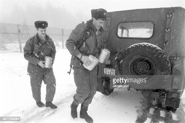 Zwei DDRGrenzsoldaten einer NVAGrenzkompanie bei Schierke am Brocken im Harz mit umgehängten Maschinenpistolen und Verpflegungsblechbüchsen im...