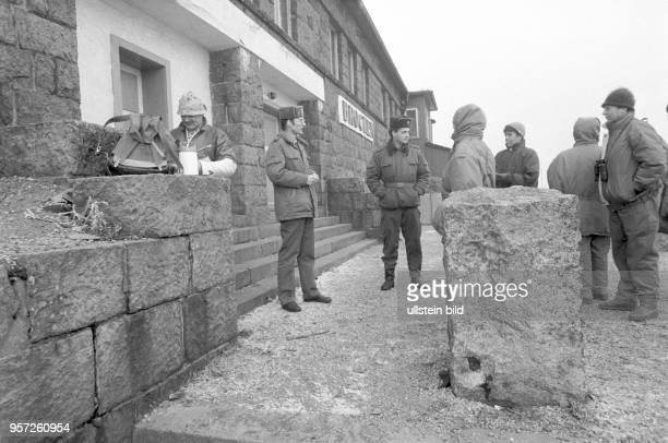 Zwei DDRGrenzsoldaten vor einem Gebäude auf dem Brocken im Gespräch mit Wanderern aufgenommen im Januar 1990 Der Brocken im Harz war bis zur...
