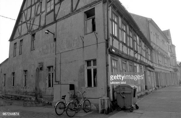 Zwei Fahrräder und eíne Mülltonne an einem verfallenen Eckhaus eines abrissgefährdeten Fachwerkhauses in der Altstadt von Stendal aufgenommen im...