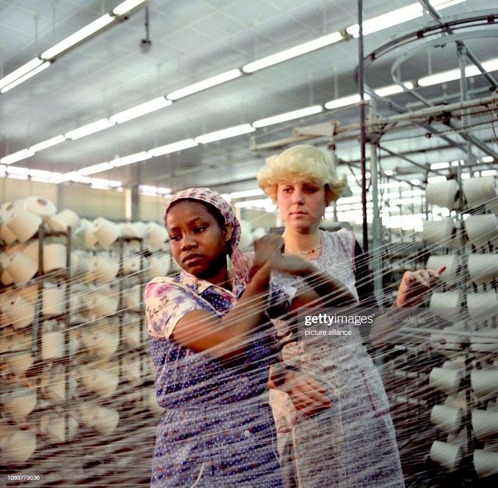 Zwei Frauen in Kittelschürzen bei der Arbeit an einer