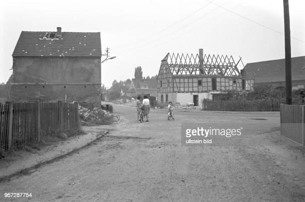 Zwei Frauen und ein Kind stehen mit dem Fahrrädern auf einer Straßenkreuzung vor abgerissenen Häusern im Ort Magdeborn der für den anrückenden...