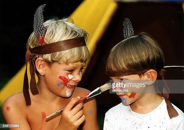 Zwei Jungen spielen Indianer sie tragen eine Feder im Haar und bemalen sich gegenseitig oJ