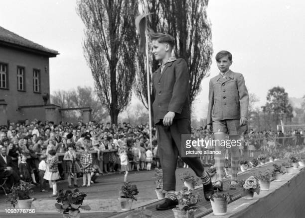 Zwei Jungen zeigen auf einem Laufsteg bei einer Modenschau elegante Kleidung für Kinder einen Anzug mit langer Hose und eine Kombination von Jacke...