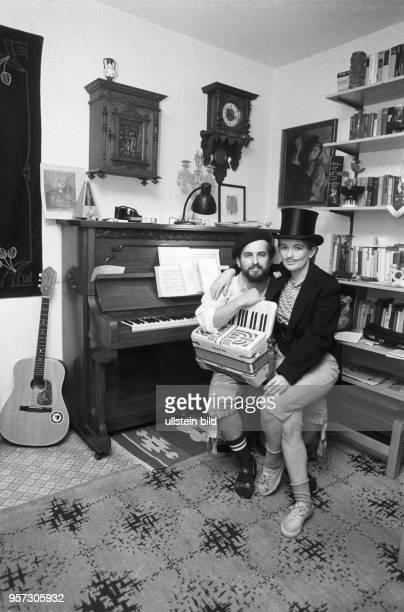 Zwei Karnevalisten posieren in ihrer Neubauwohnung im ErnstThälmannPark in Berlin in einer gemütlich eingerichteten Ecke mit Klavier und Wandregal...