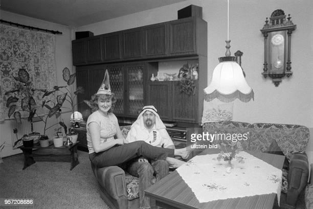 Zwei Karnevalisten posieren in ihrer Neubauwohnung im ErnstThälmannPark in Berlin zwischen Schrankwand und Sitzeckel aufgenommen 1987 Die...