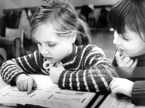 Zwei Kinder beim Rechnen über ihren Schulbüchern in einer 1 Klasse einer Schule in der DDR aufgenommen 1976 Foto Günter Gueffroy dpa Report