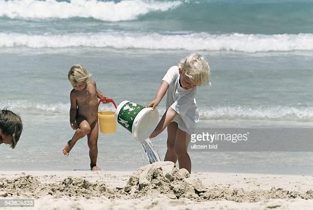 Zwei kleine Kinder das eine nur mit einem weißen Shirt bekleidet das andere ein Nackedei spielen am Strand nahe dem Meer Sie haben die Eimer mit...