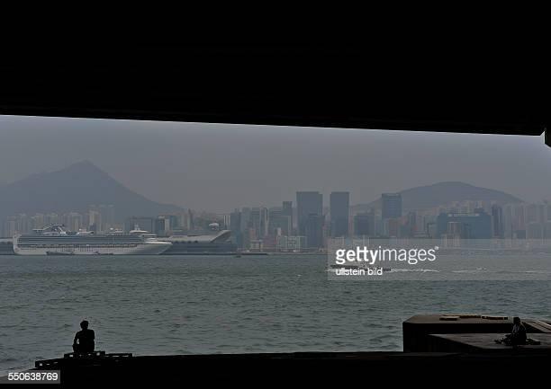 Zwei Maenner sitzen am Ufer und blicken nach Kowloon auf den neuen Passagier Terminal am ehemaligen Flughafen