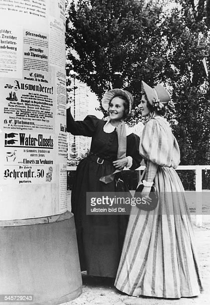 zwei Mädchen in Biedermeierkleidern vor einer alten LitfassSäule August 1937